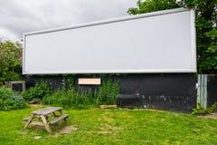 Un grand panneau d'affichage vide vide du côté de la route avec le banc dedans image libre de droits