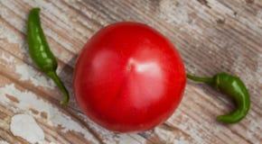 Un grand poivre vert pointu mûr organique de tomate et de piment deux sur une table de cuisine en bois rustique Vue supérieure Photo libre de droits