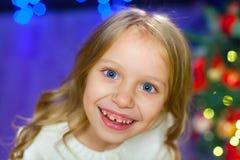 Un grand portrait d'un enfant sur un fond des lumières de Noël Image stock