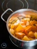 Un grand pot courant sur un fourneau avec des légumes coupés pour faire la soupe, légumes cuits à la vapeur avec la minuterie photographie stock