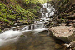 Un grand rocher se trouve au pied d'une cascade dans les montagnes carpathiennes Photographie stock