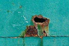 Un grand trou rouillé sur une porte en métal de sarcelle d'hiver image stock
