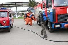 Un grand véhicule de sauvetage du feu rouge, un camion pour s'éteindre un feu et des sapeurs-pompiers de mâle sont préparés pour  images libres de droits