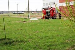 Un grand véhicule de sauvetage du feu rouge, un camion pour s'éteindre un feu et des sapeurs-pompiers de mâle sont préparés pour  images stock