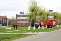 Un grand véhicule de sauvetage du feu rouge, un camion pour s'éteindre un feu et des sapeurs-pompiers de mâle sont préparés pour  photographie stock
