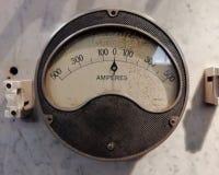 un grande amperometro industriale d'annata rotondo con un quadrante analogico con i numeri con i simboli elettrici standard su un fotografia stock libera da diritti