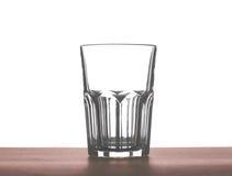 Un grande bello vetro vuoto per acqua, succo o latte su una tavola di legno di marrone scuro, isolata su un fondo bianco Immagini Stock Libere da Diritti
