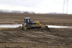 Un grande bulldozer scava un canale di bonifica Fotografia Stock