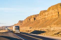 Un grande camion che guida nel tramonto con il fondo della montagna Immagini Stock Libere da Diritti