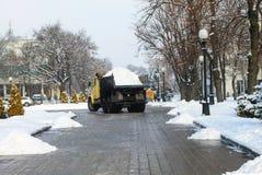 Un grande camion pratico rimuove la neve da una via della città nell'inverno Città di Dnipro, Dniepropetovsk, fotografia stock libera da diritti