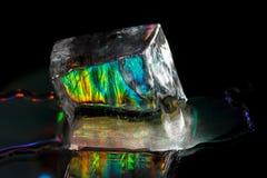 Un grande cubetto di ghiaccio variopinto isolato sul nero Immagini Stock
