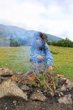 Un grande fuoco di picnic nel legno ed in una donna vicino  fotografia stock libera da diritti