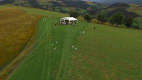 Un grande gruppo di persone sta facendo una pausa la tenda bianca nel campo video d archivio