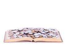 Un grande libro aperto con le monete Fotografia Stock