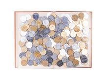 Un grande libro aperto con le monete Fotografie Stock Libere da Diritti