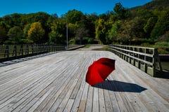 Un grande ombrello rosso su un ponte di legno Fotografia Stock