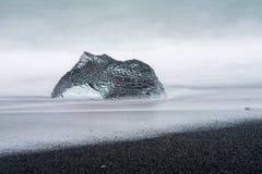 Un grande pezzo astratto di ghiaccio del ghiacciaio si siede su una spiaggia di sabbia nera in Islanda Immagini Stock Libere da Diritti