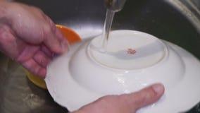 Un grande piatto è lavato nel lavandino con il detersivo archivi video