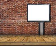 Un grande tabellone per le affissioni in bianco allegato ad un muro di mattoni dentro con il pavimento di legno fotografia stock