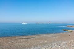 Un grande yacht bianco entra nel porto Pebble Beach abbandonato immagini stock