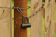 Un grands vieux cadenas et chaîne sur un tuyau et un conseil en bois images libres de droits