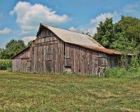 Un granero abandonado viejo en el país con un cielo azul y nubes blancas Fotos de archivo