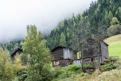 Un granero de madera en la colina rodeada por la cabaña vieja del bosque del abeto en la montaña dentro de la nube, ambiente natu imagen de archivo libre de regalías