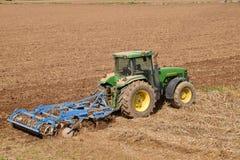 Un granjero con un tractor que ara la tierra antes de 070 de siembra Foto de archivo