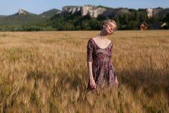 Un granjero de la mujer en el campo de la cosecha del trigo fotos de archivo