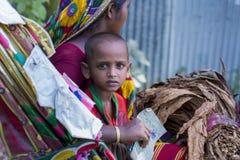 Un granjero de sexo femenino del tabaco y su niño que van a comercializar la venta para secar la hoja del tabaco Fotografía de archivo libre de regalías