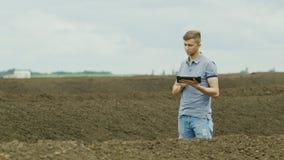 Un granjero joven está trabajando cerca de una pila de estiércol vegetal que explica los fertilizantes orgánicos, agricultura sin almacen de metraje de vídeo