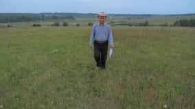 Un granjero mayor In The Hat, caminando en The Field que sostiene un teléfono y una carpeta almacen de video