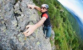 Un gratuit-grimpeur atteint le dessus d'un mur rocheux Concept : courage photographie stock