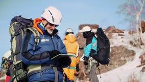 Un grimpeur expérimenté avec la barbe blanche et les lunettes de soleil est au repos et regardant le comprimé la manière banque de vidéos