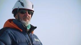 Un grimpeur expérimenté utilisant un casque et des lunettes de soleil se tient sur le dessus et apprécie la vue, regards et souri banque de vidéos