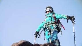 Un grimpeur fier se tient au bord de la roche avec ses bras aux côtés, se réjouissant dans la victoire banque de vidéos