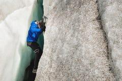 Un grimpeur libre sans assurance avec deux haches de glace se lève d'une fente dans le glacier Free s'élevant sans cordes images libres de droits