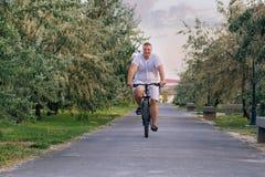 Un gros homme monte une bicyclette le long du mail au cours de la journée photographie stock
