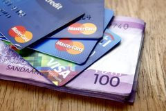Un groupe cartes de crédit de MasterCard et de visa et cent factures de peso philippin sur une table Photographie stock