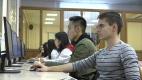 Un groupe d'étudiants asiatiques et européens utilisent des ordinateurs dans la salle de classe banque de vidéos