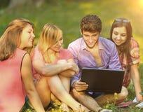 Un groupe d'étudiants avec l'ordinateur portable détendant en parc le jour ensoleillé Images stock