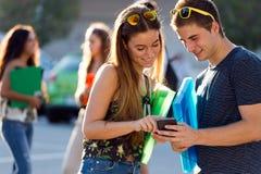 Un groupe d'étudiants ayant l'amusement avec des smartphones après classe Photo stock