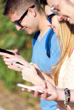 Un groupe d'étudiants ayant l'amusement avec des smartphones après classe Images libres de droits