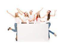 Un groupe d'adolescents heureux et émotifs dans le posin de chapeaux de Noël Photographie stock libre de droits