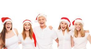 Un groupe d'adolescents heureux et émotifs dans le posin de chapeaux de Noël Image libre de droits