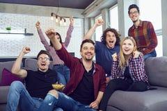 Un groupe d'amis à une partie regardant la TV Image stock