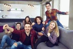 Un groupe d'amis à une partie regardant la TV Photos stock