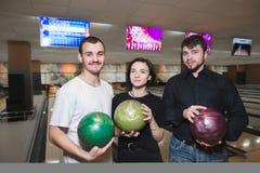 Un groupe d'amis avec des boules de bowling dans leurs mains posent au club de bowling Images libres de droits