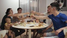 Un groupe d'amis avec des enfants, les jeunes s'asseyant à une table à un dîner, buvant banque de vidéos