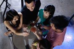 Un groupe d'amis ayant des boissons dans la boîte de nuit Photographie stock libre de droits